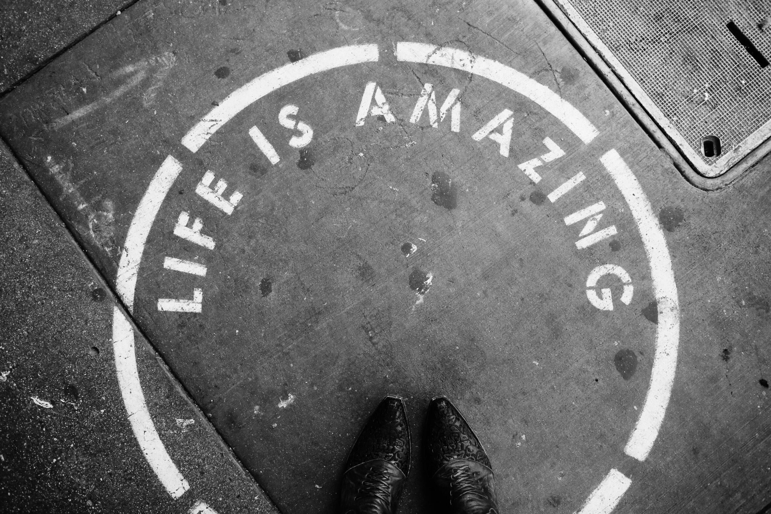 person wearing leather shoes stepping on Life is Amazing circle texts